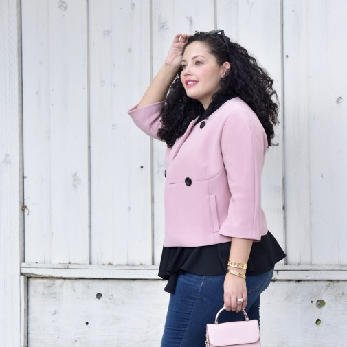 Girl With Curves blogger Tanesha Awasthi wears a pink cropped jacket, peplum top, pink bag and skinny jeans.