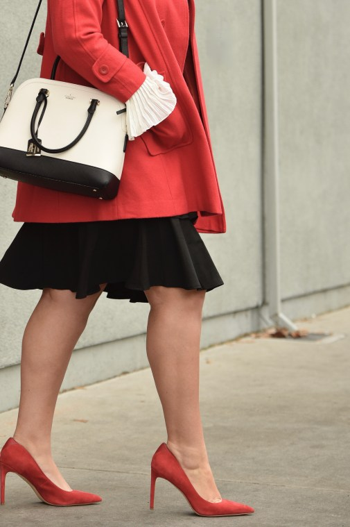 Girl With Curves blogger Tanesha Awasthi wears a plus size ruffle skirt, bell sleeve blouse, red swing coat, kate spade bag and red pumps.