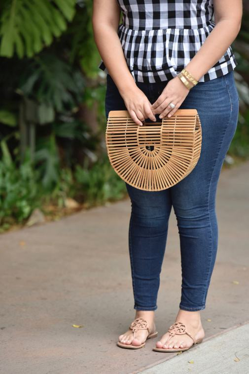 Girl With Curves blogger Tanesha Awasthi wears a gingham peplum, skinny jeans, Tory Burch Miller sandals, wicker bag and boater hat in Hawaii.