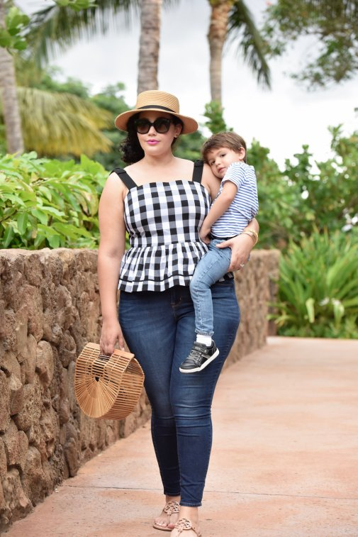 Girl With Curves blogger Tanesha Awasthi wears a gingham peplum and boater hat in Hawaii with her son Narayan.