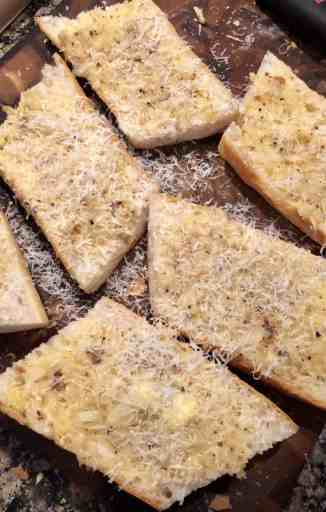 garlic butter spread over french bread with fresh parmesan over the top