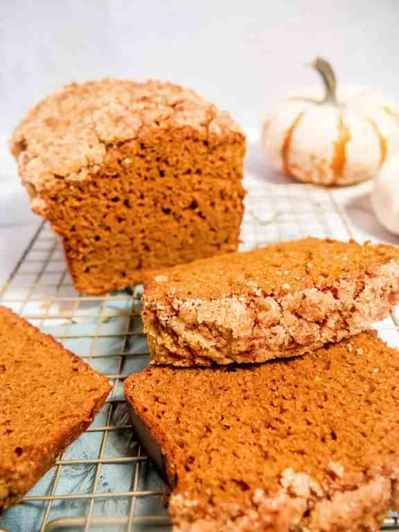 pumpkin bread loaf and pumpkin bread slices laying on top of eachother with a crumble topping and a pumpkin in the background