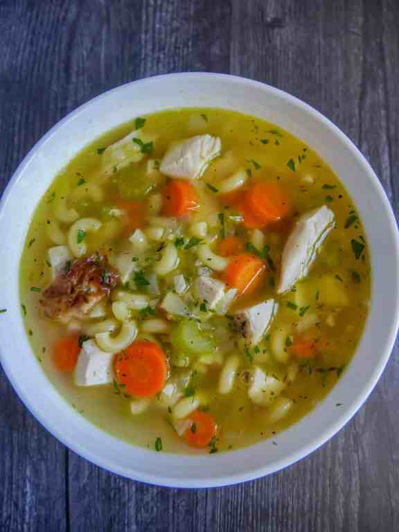 bowl of chicken noodle soup with parsley garnish