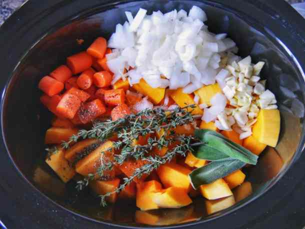slow cooker filled with butternut squash soup ingredients