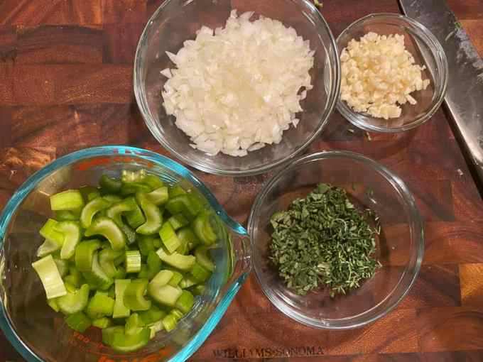 bowls of chopped celery, onion, garlic, and fresh herbs