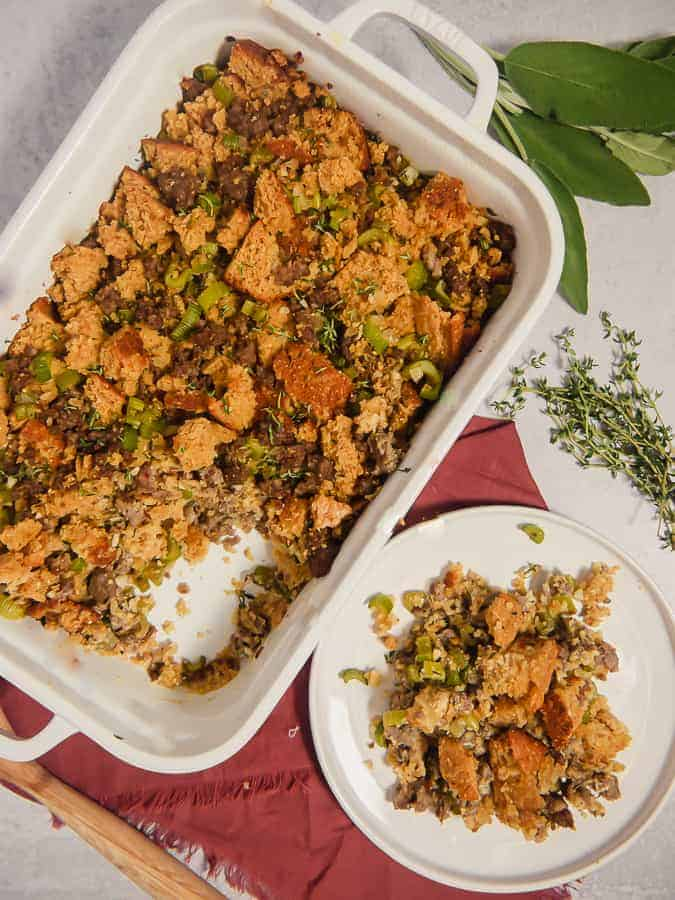 white baking dish with cornbread stuffing and a smaller plate with cornbread stuffing inside.