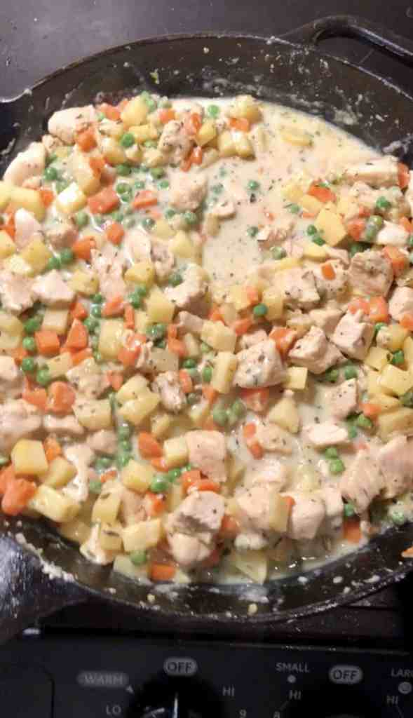 photo of chicken pot pie filling with potatoes, carrots, peas, and chicken in a cast iron skillet