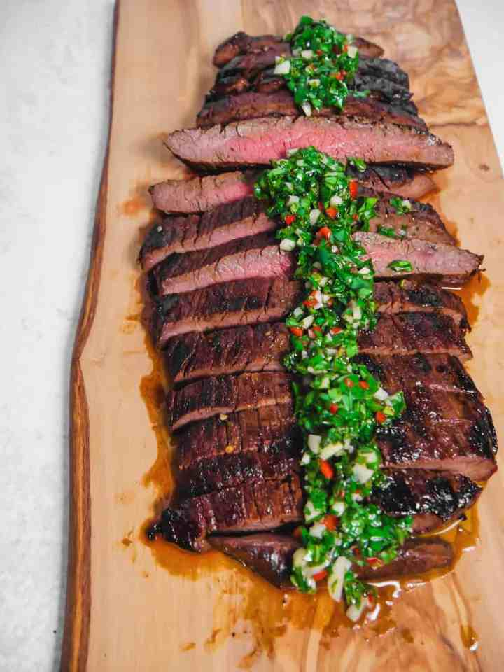 sliced grilled flank steak with chimichurri over the top on a cutting board