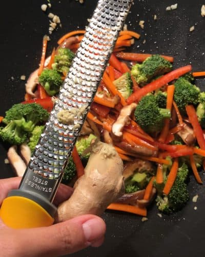 grating ginger into a wok for lo mein