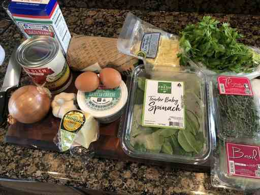 spinach and beef lasagna ingredients laid out on a cutting board