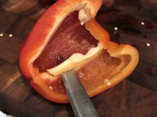 cutting the inside of a pepper with a pairing knife