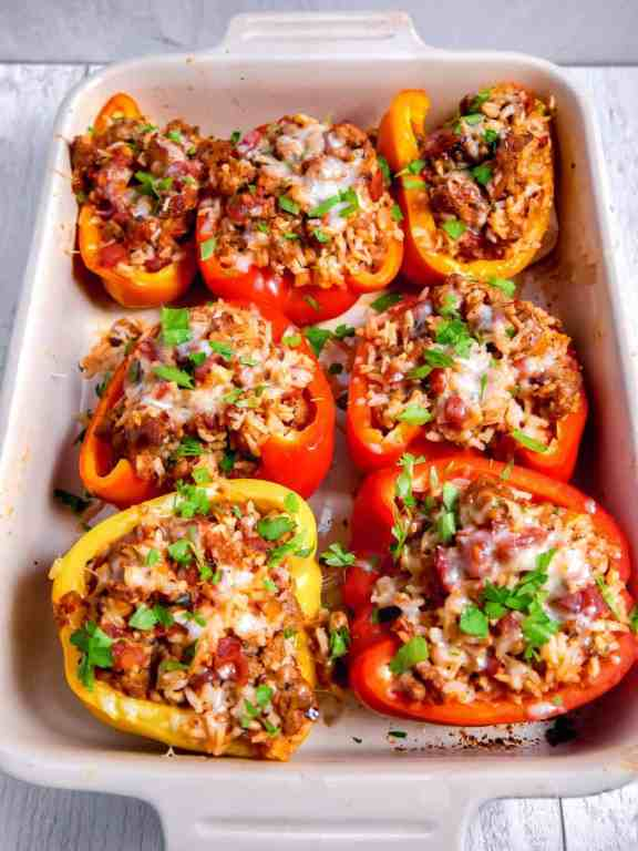 overhead shot of cooked stuffed peppers with melted cheese and fresh herbs sprinkled over the top