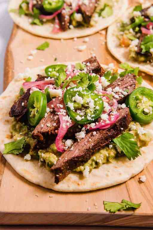 close up shot of open faced tortilla with guacamole, grilled skirt steak, pickled red onions, and sliced jalapenos with cotija cheese on top
