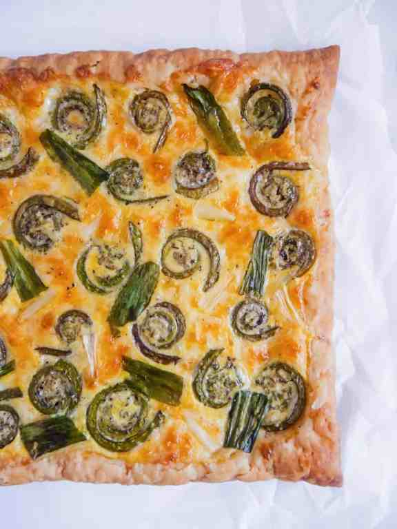 overhead half shot of cooked puff pastry cheese tart with roasted fiddlehead ferns and ramps on parchment paper