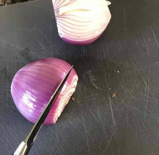peeled and halved red onion with a knife slicing off a slice on a grey cutting board