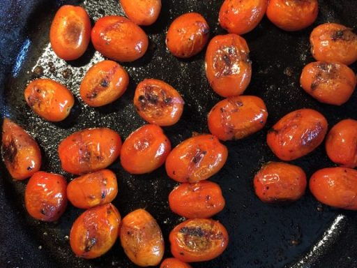 blistered tomatoes in a cast iron skillet