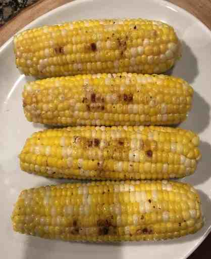 overhead shot of grilled ears of corn with char marks on a white plate