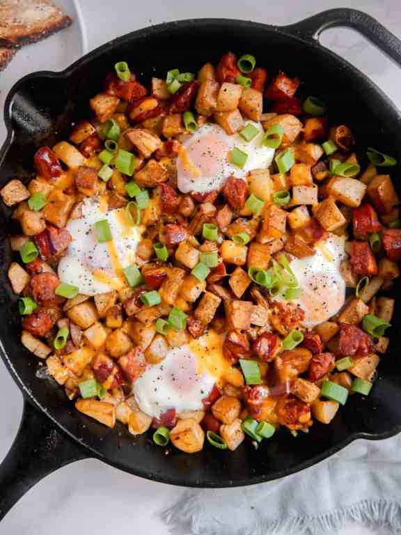 overhead shot of breakfast potatoes, chorizo, baked eggs, and green onions in a cast iron skillet