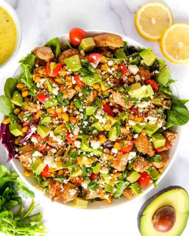 overhead shot of the Mexican garden chicken salad with lettuce, chicken, avocado, corn, tomatoes, in a white bowl with cotija cheese over the top