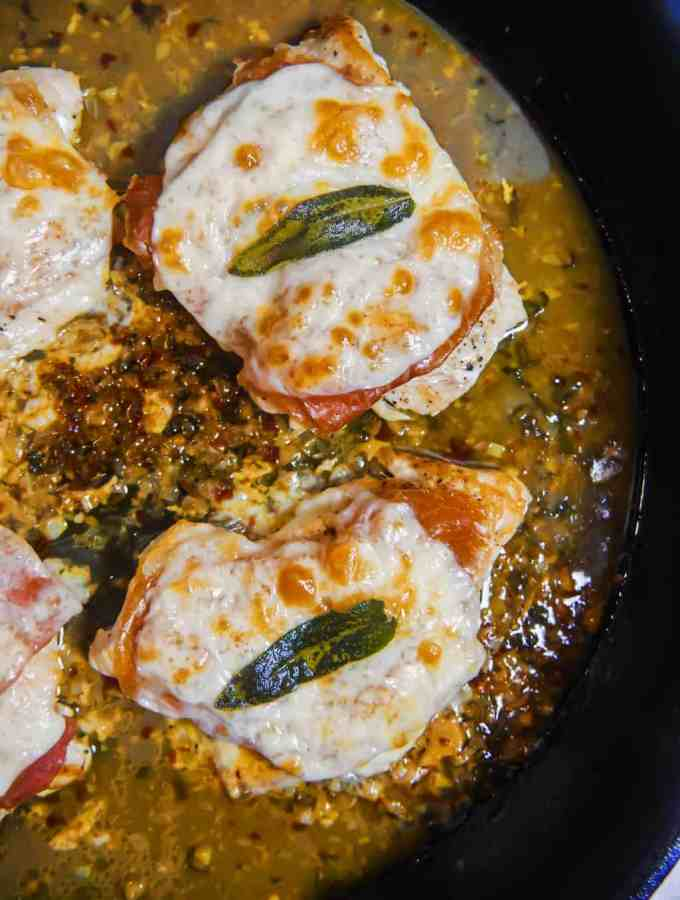 overhead shot of a cast iron skillet with chicken breats covered in prosciutto , browned bubbly cheese, sage leaves, surrounded by a golden sauce