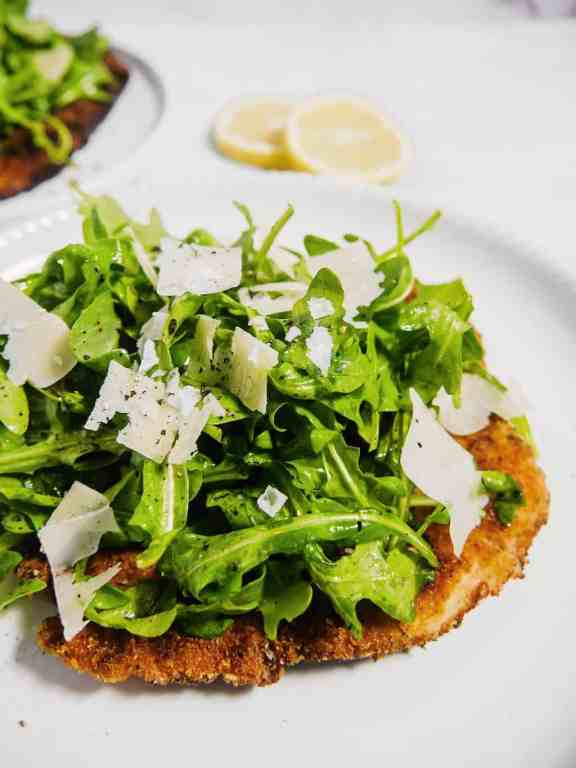 front shot of chicken milanese on a white plate with arugula piled on top and shaved parmesan