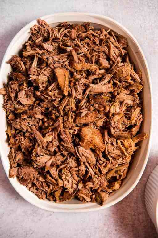 overhead shot of a white baking dish with shredded pulled pork inside