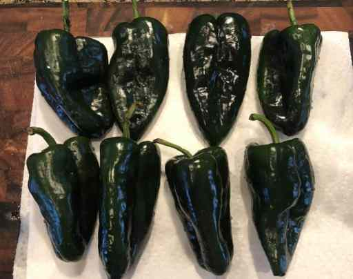 whole poblano peppers on a cutting board