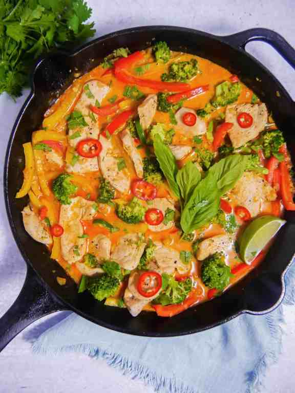 overhead of a cast iron skillet with red coconut curry broth, chicken, broccoli, chilis, basil, with a blue background