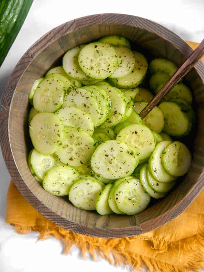 overhead shot of sliced cucumbers in a wooden bowl with a spoon in the center, laying on top of a gold towel