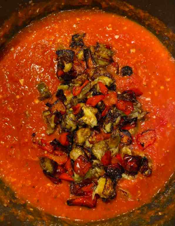 overhead shot of red sauce with roasted eggplant and bell peppers inside