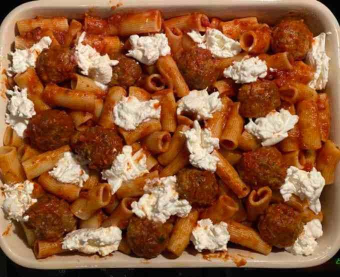 rigatoni pasta, meatballs, and burrata cheese in a baking dish