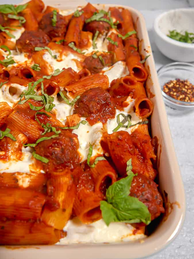 close up of meatball pasta bake in a casserole dish with crushed red pepper flakes and basil in the background