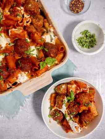 overhead photo of meatball pasta bake in a casserole dish and a bowl of rigatoni and meatballs
