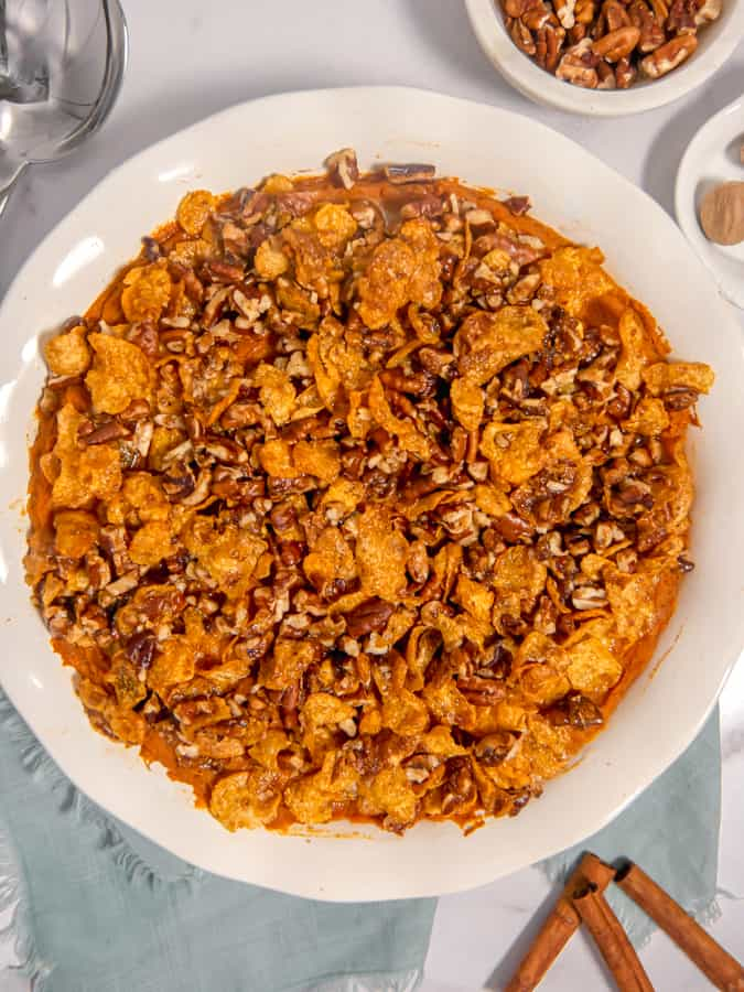 overhead photo of a sweet potato casserole with brown sugar crunchy pecan and cornflake topping in a white dish with cinnamon sticks, nutmeg, and pecans surrounding