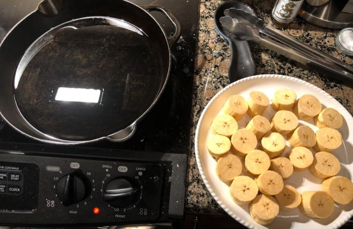sliced plantains on plate next to cast iron with oil