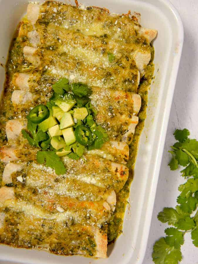 overhead shot of enchiladas in a white baking dish with verde sauce, melted cheese, cilantro and avocado