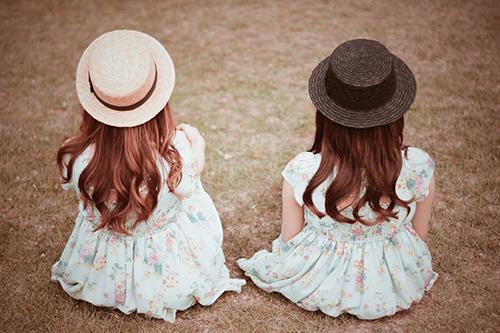 「友達」「双子ルック」「女性・女の子」「巻き髪」「春」「芝生」「花」「花かんむり」「草原」などがテーマのフリー写真画像