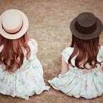 フリー写真素材:草原に座って景色を見ている双子の女の子たち