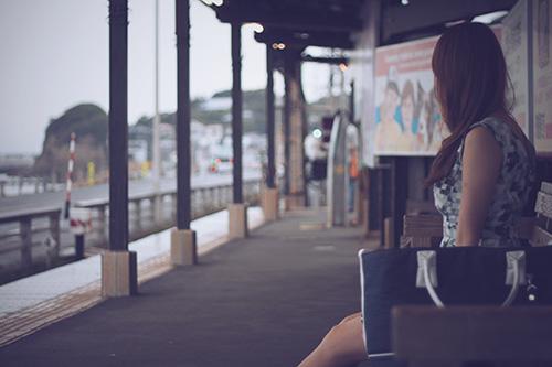 「女性・女の子」「巻き髪」「梅雨」「雨」「駅のホーム」などがテーマのフリー写真画像