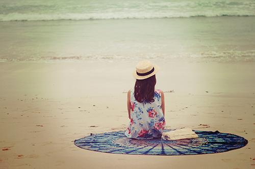 「ビーチ」「ラウンドタオル」「夏」「女性・女の子」「巻き髪」「帽子」「海」「砂浜」「麦わら帽子」などがテーマのフリー写真画像