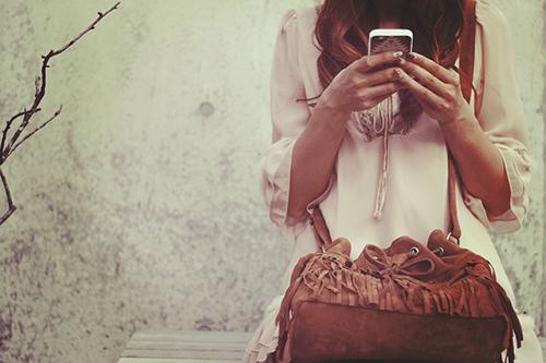 「iPhone」「ショルダーバッグ」「スマートフォン」「フリンジ」「女性・女の子」「巻き髪」「秋」「鞄」などがテーマのフリー写真画像
