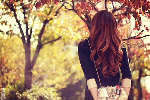 紅葉に見とれている秋の日の女の子