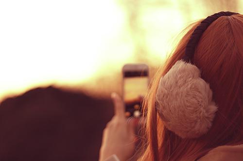 iPhoneで冬の夕焼けを撮影するイヤーマフな女の子