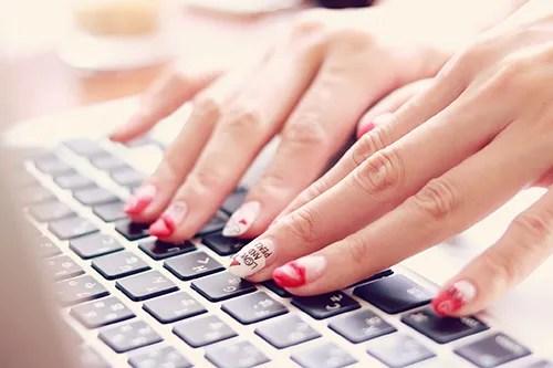 パソコンでタイピングをするネイルが可愛い女の子