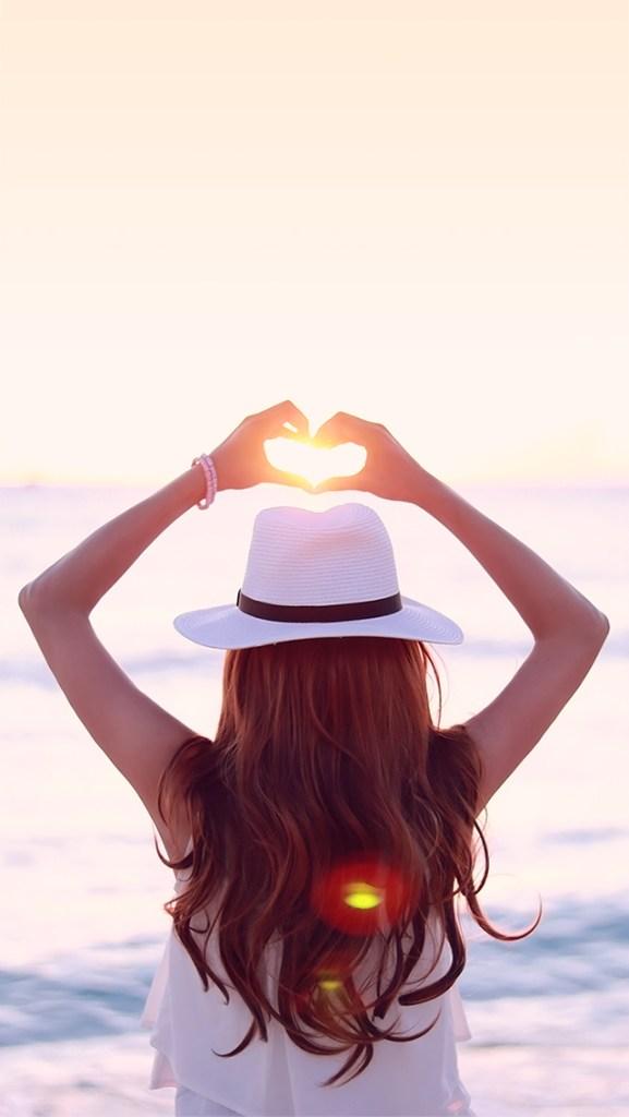 【オシャレなiPhone壁紙】海に落ちていく夕陽にハートの手をかざす女の子