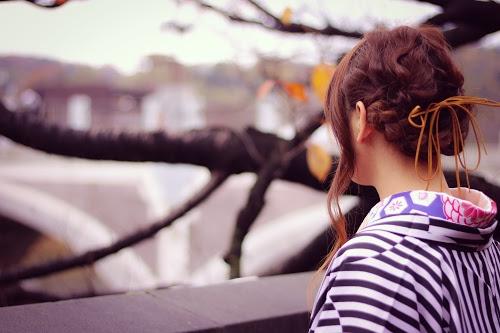 川辺で向こう岸を見つめる着物姿の女の子