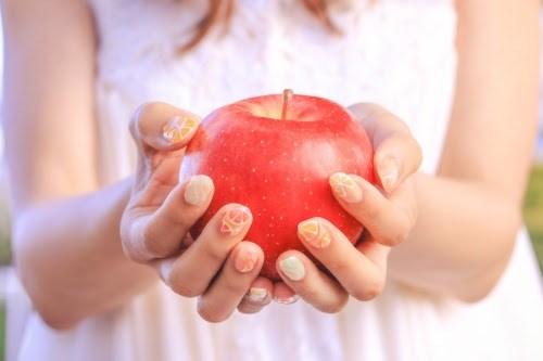 両手でりんごを持つ女の子