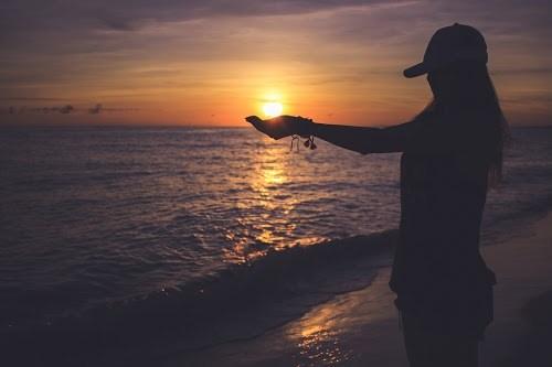 宮古島の夕日スポット与那覇前浜ビーチで、手のひらに夕日をのせて遊んでいる女の子