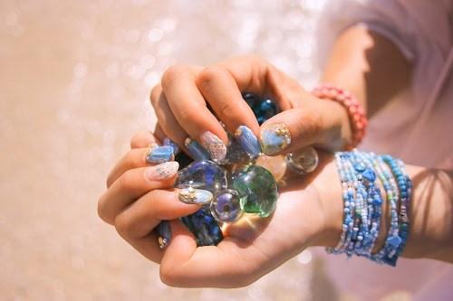 「ガラス玉」「シェルネイル」「ネイル」「ネイルアート」「ブレスレット」「マーメイドネイル」「リゾート」「南国」「夏」「夏ネイル」「手」「波打ち際」「海」「海ネイル」「砂浜」「金魚の鱗ネイル」「雑貨」などがテーマのフリー写真画像