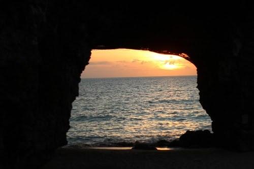 隆起サンゴがつくりあげた天然のアーチ越しの夕焼け